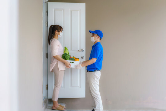 Asian woman costumer wearing face mask and glove receive groceries box of food, fruit, vegetable and drink from delivery man   in front of the house during time of home isolation.
