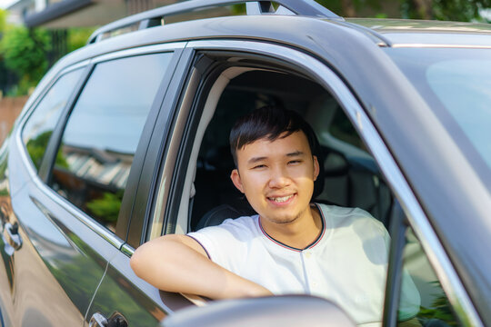Asian happy young handsome man driving a car in front seat with smile prepare to journey with his car..