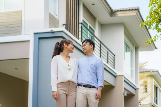 Portrait of Asian young couple standing and hugging together looking happy in front of their new house to start new life. Family, age, home, real estate and people concept.