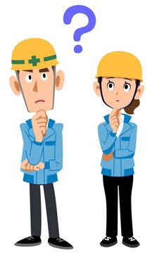 疑問を持つ建築現場作業員男女の全身