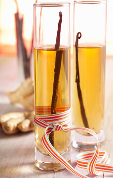 Homemade vanilla and ginger vinegar in cylindrical glasses with a bow
