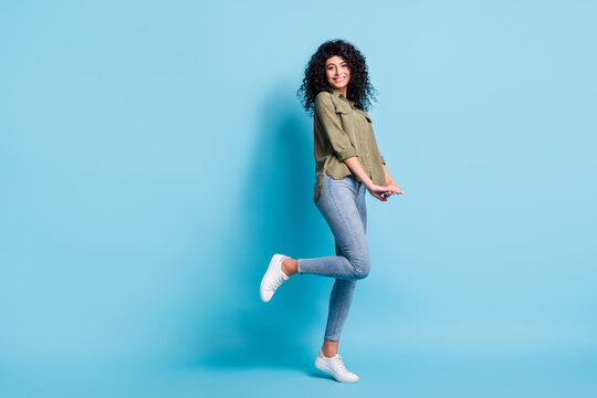 Full body profile photo of gorgeous person toothy smile bent feet isolated on pastel blue color background