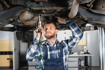 mechanic fixing detail with pneumatic wrench while standing under raised car, stock image