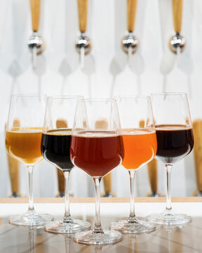 Different types of beer displayed in wine glasses