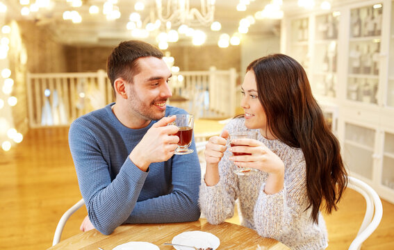 people, communication and dating concept - happy couple drinking tea at cafe or restaurant over festive lights background
