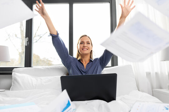 remote job, work and business concept - happy smiling young woman with laptop computer throwing papers in bed at home
