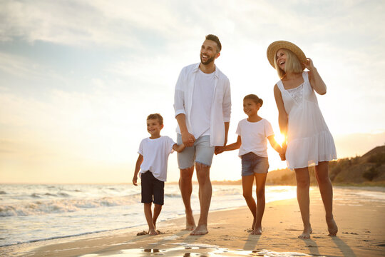 Happy family walking on sandy beach near sea at sunset