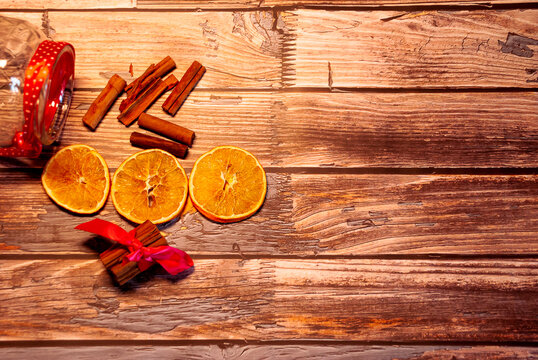 Dried oranges with cinnamon on a wooden table