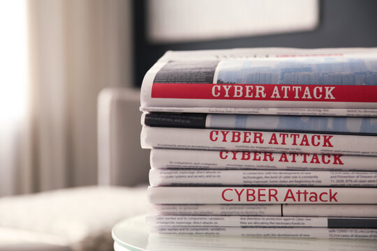 Stack of newspapers with headlines CYBER ATTACK on table indoors, closeup