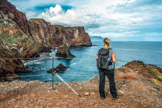 Girl hiking rocky cliffs clear near water of Atlantic Ocean bay Ponta de Sao Lourenco, the island of Madeira, Portugal