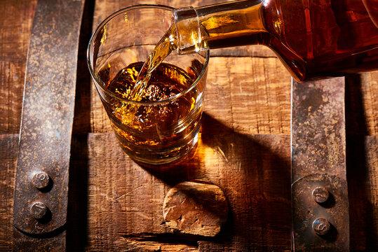 Bourbon pouring into rocks glass on a bourbon barrel