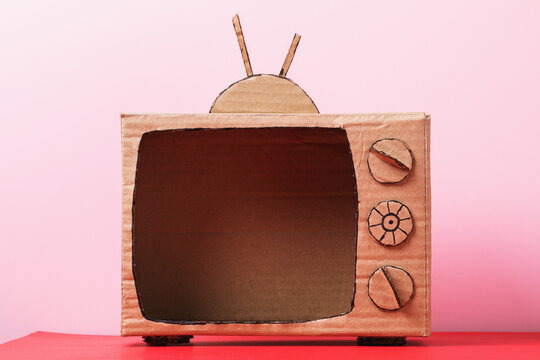 Blank cardboard TV on a pink background. Concept on the topic of television