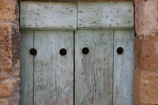 gray painted wooden door with four holes in a stone wall