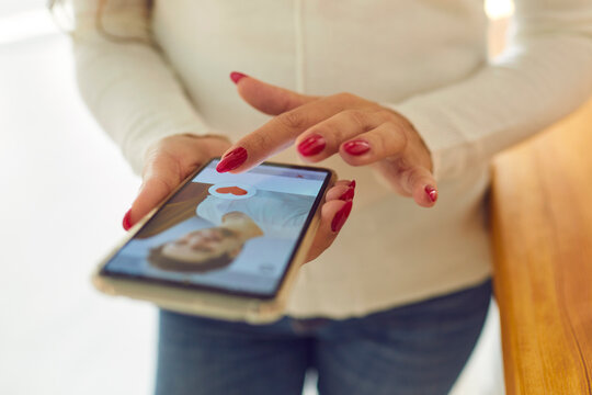 Womans hands hands choosing male profile in online dating application on smartphone