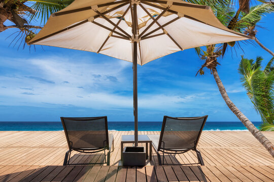 Paradise Sunny beach with umbrella and deckchairs on wooden floor, palm trees and the turquoise sea on Tropical island