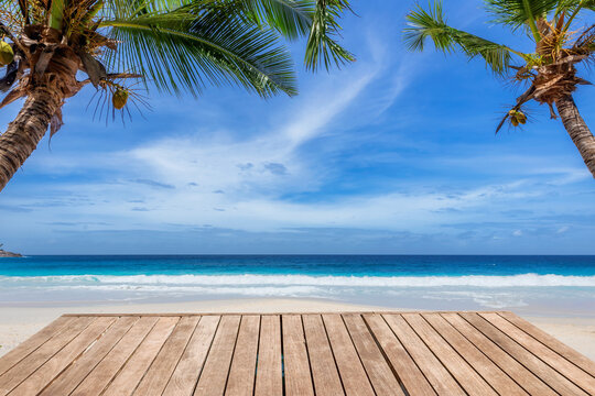 Empty wooden table and coconut palms with party on tropical beach background.  Concept of beach party in summer vacations.