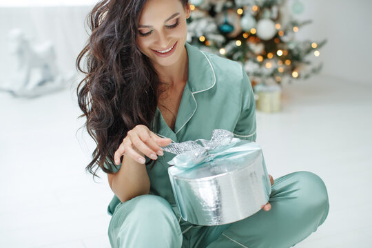 Beautiful sexy young woman sitting next to a Christmas tree holding a present present. Christmas photo. High quality photo.