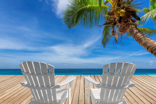 Vacations tropical Sunny beach with white beach chairs on wooden floor, palm trees and the turquoise sea on Paradise island.