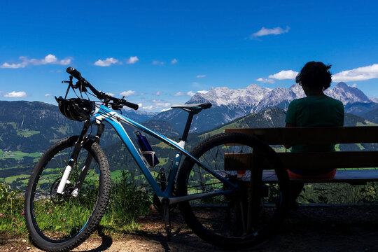 Mountainbikerin macht eine Pause im Schatten mit Blick auf die Berge und in das Tal