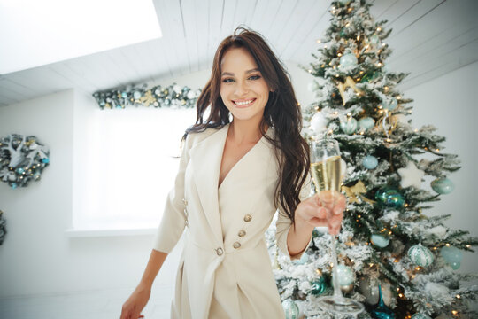Smiling woman with glass of sparkling wine under Christmas tree lights background. High quality photo
