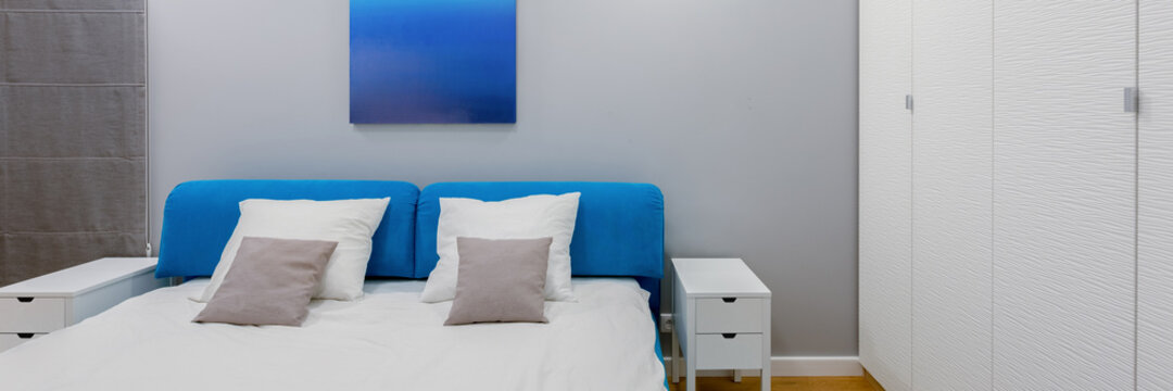 Modern bedroom in white and blue, panorama