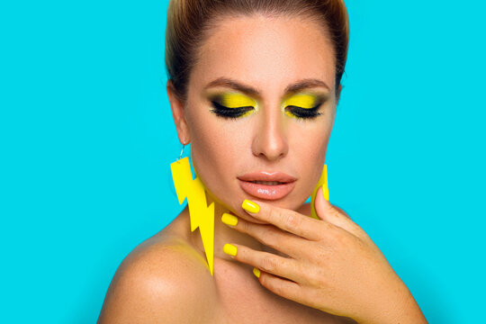Beautiful girl with bright makeup and yellow manicured nails isolated blue background. Closeup portrait of blonde with lightning flat earrings jewelry.