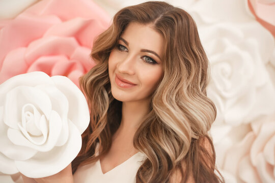 Beautiful hair. Woman beauty portrait smiling with makeup and long healthy hairstyle over pink white roses flowers.