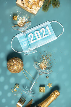 Two champagne glasses with splash of confetti, gifts and decorations over creative background