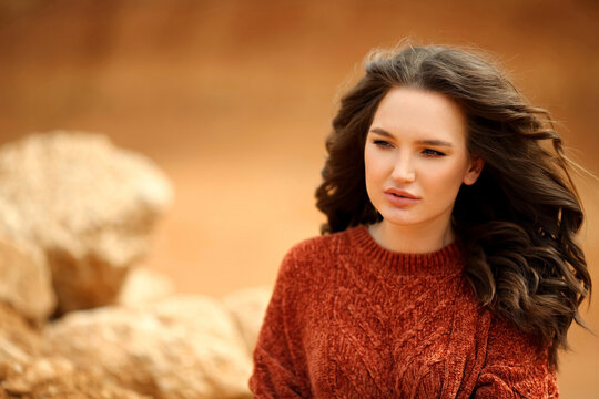 Woman outdoor portrait. Young beautiful brunette in warm cozy knitted clothes.  Autumn. Soft colours.