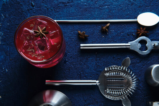 Red drink with ice cubes and set of bartender equipment on blue table