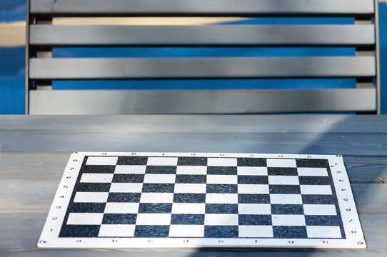 Empty chess board table with park bench. Outdoor activities concept
