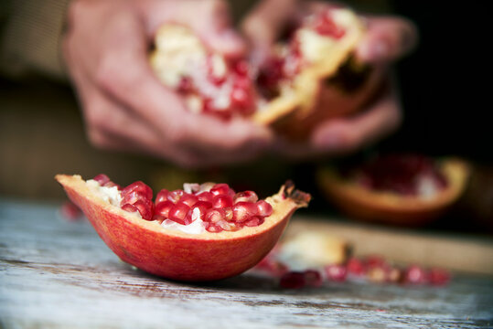 man opening a pomegranate fruit