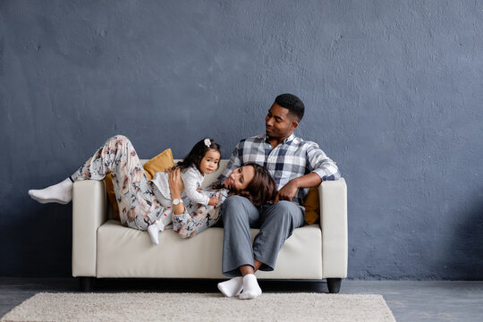 Happy positive mixed race family african-american young father asian mother and little daughter resting at home sitting on the sofa against the background of a gray wall. Advertising space