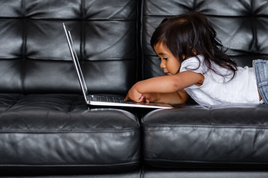 Side view of talented little mixed race girl pushing button on laptop while looking at cartoons while lying on an armchair. Concept of independent children and gadgets. Children and internet addiction