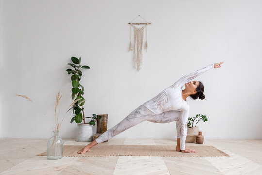 Side view of slim pretty positive young brunette woman doing Utthita parsvakonasana exercise, Extended Side Angle pose, on mat on floor surrounded by houseplants on white wall. Advertising space.