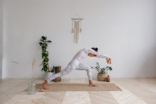 Side view of a slim pretty positive young brunette woman doing a virabhadrasana standing on the mat on the floor surrounded by houseplants on a white wall. Advertising space. Yoga and pilates