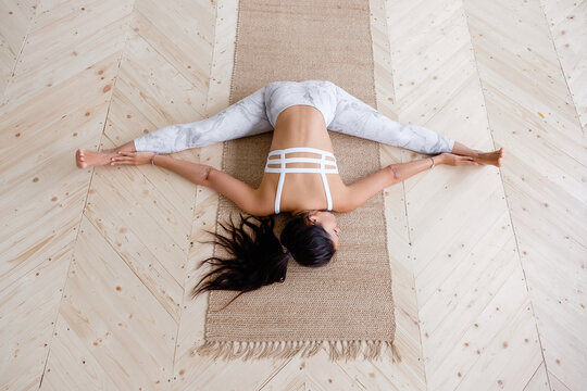 Top view flexible slim young unknown caucasian brunette woman doing manducasana lying on a rug on a wooden floor. Concept of flexibility for joints and ligaments. Advertising space