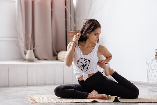 Flexible concentrated beautiful young brunette doing eka pada rajdakapotasana sitting on a rug on the floor in sportswear in an empty room. Concept of improving joints and rejuvenating the body
