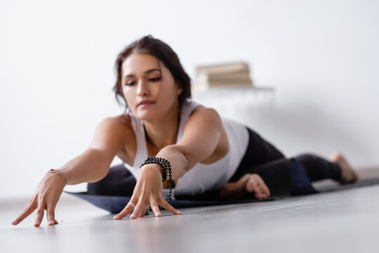 Relaxed positive young woman doing stretching and enjoying body recovery with eyes closed. Concept of improving the health and blood supply to the body. Stretching and Pilates at home