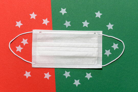 Non-medical face mask in Christmas sphere with a red green background, white stars and space for text