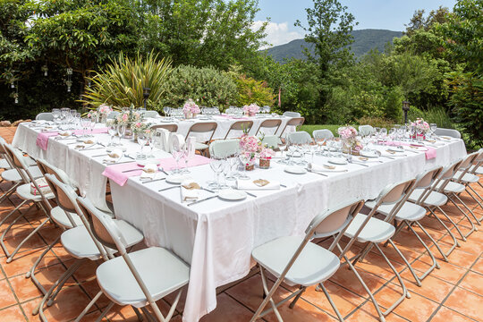 Wedding table decorated with bouquet of pink flowers and wine glasses.