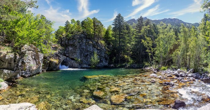 Scenic view of waterfall and lake in a Spanish Pyrenees Mountain in a sunny day. Transparent clear water.Aiguestortes i Estany of Saint Maurici National Park