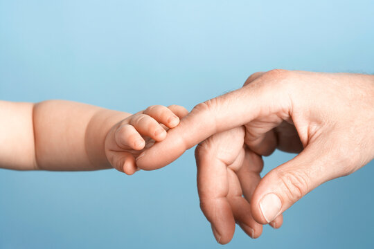 Closeup Of Baby Holding Man's Finger