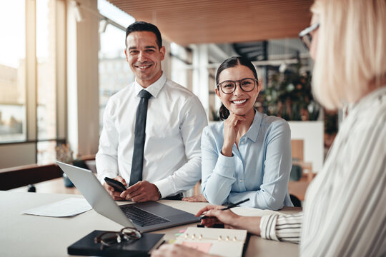Smiling young businesswoman working with colleagues in an office