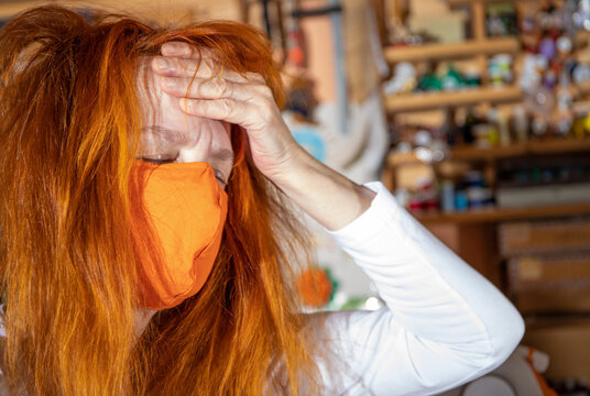 A red-haired woman is wearing a medical respirator, she is exhausted
