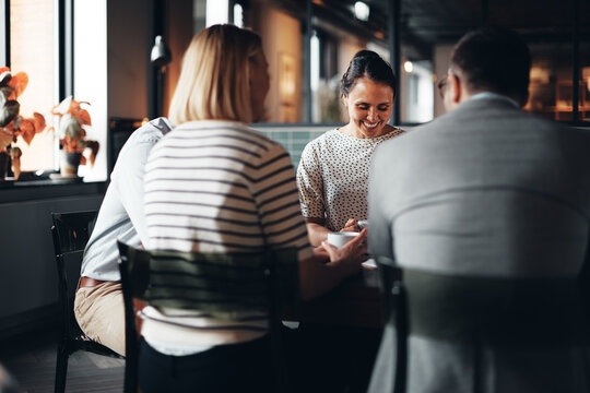 Smiling businesswoman having coffee with coworkers
