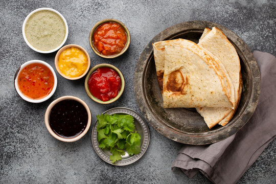 Assorted Indian chutneys in rustic bowls and flatbread on grey concrete background