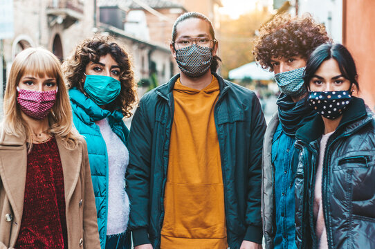 New normal lifestyle concept with multiracial people covered by face mask walking on city street - Focus on guy on the middle