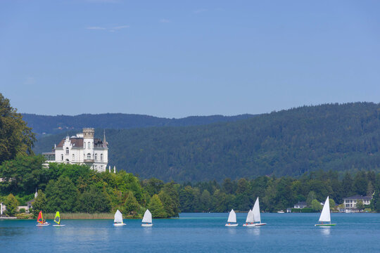 Boating and sailing on the clear waters of alpine Lake Worthersee, famous tourist attraction for many water activity, in Carinthia region, Austria
