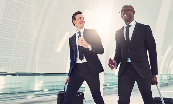 Two smiling businessmen walking through an airport talking together